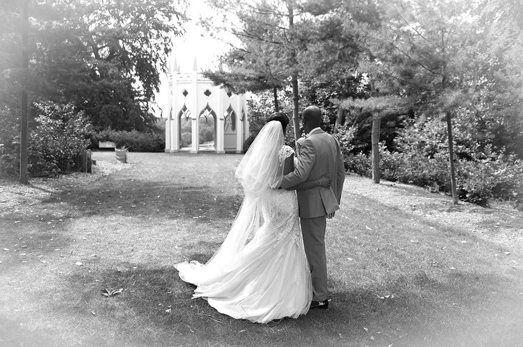 Bride and Groom romantically standing together at Surrey wedding venue Painshill Park looking across the lawn towards the magical Gothic Temple