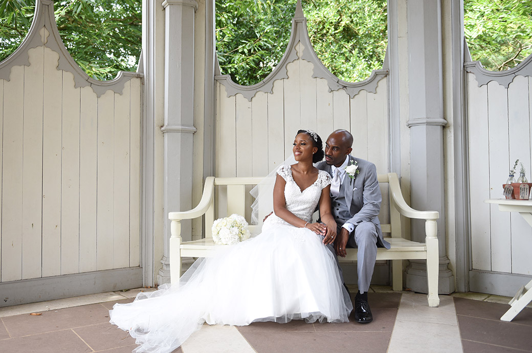 Handsome newlywed couple at Surrey wedding venue Painshill Park savour the moment in the Gothic Temple as they sit on a bench looking out over the wonderful view