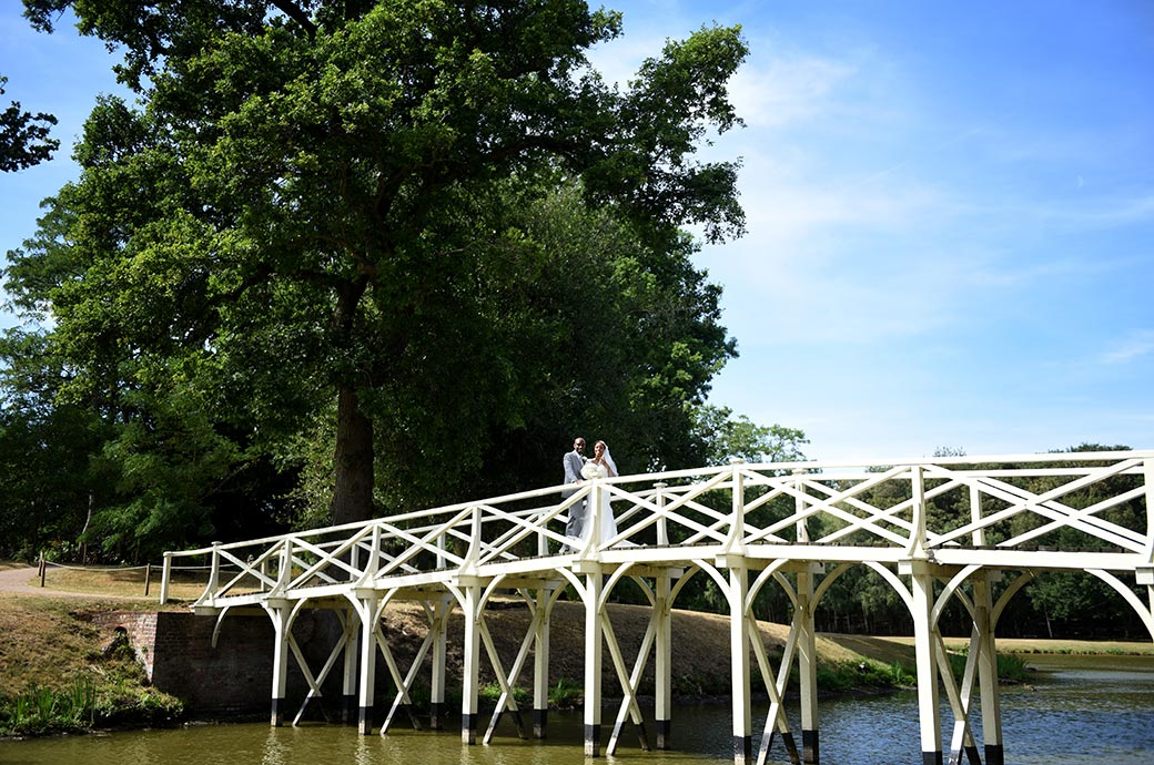 A picture of a Bride and groom standing on the white wooden Chinese Bridge captured at the scenic Surrey wedding venue Painshill Park in Cobham