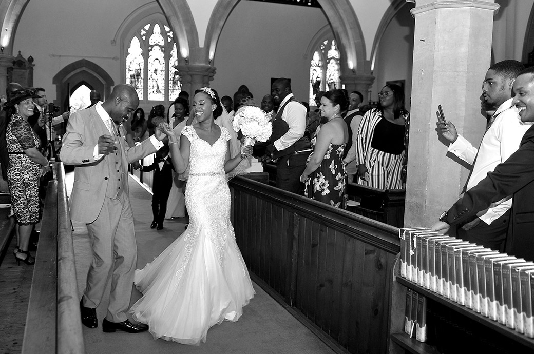 Wonderful wedding picture of a very happy couple dancing through the church on route for their Surrey reception at the Painshill Park Conservatory