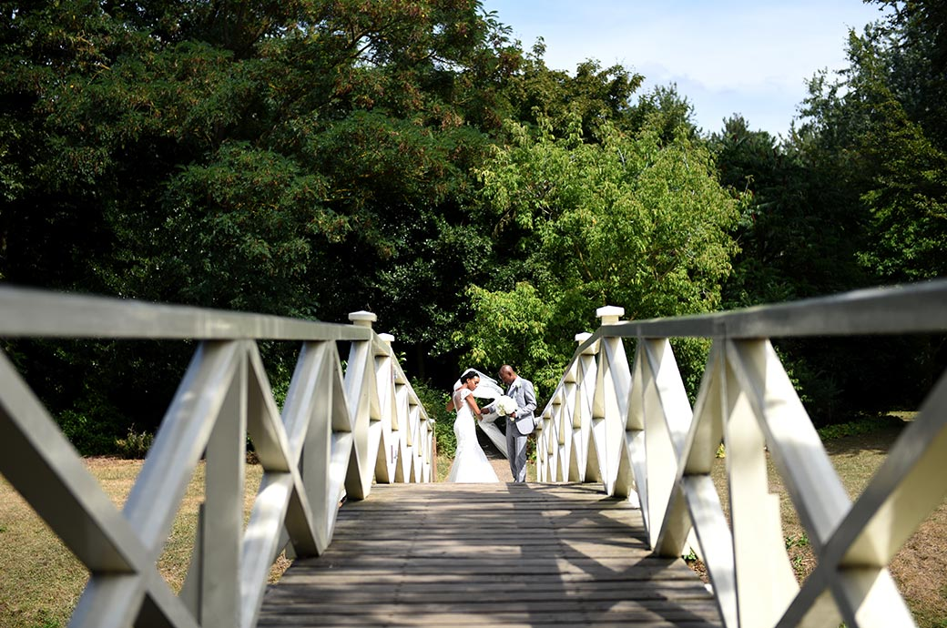 Wedding photograph of a Groom helping his Bride at the wonderfully scenic Surrey venue Painshill Park with her blowing veil as they cross the Chinese Bridge