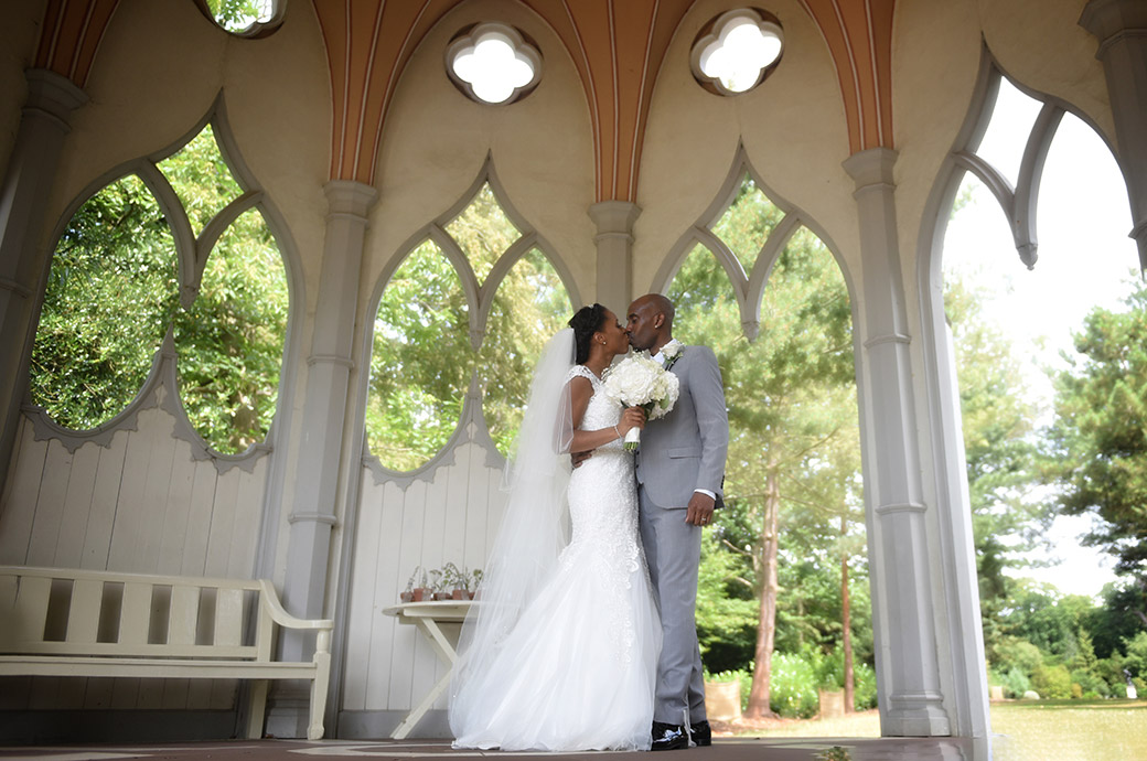 Wonderfully romantic picture of a handsome couple at the Painshill Park wedding venue in Cobham Surrey kissing in the magical Gothic Temple
