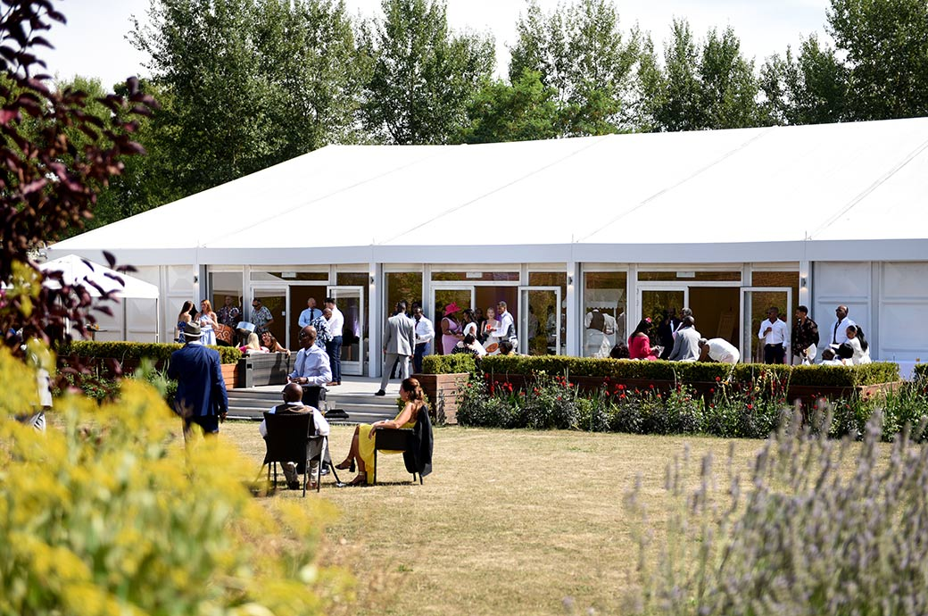 View through the bushes of guests relaxing out on the lawn and outside The Conservatory in the lovely Walled Garden at Surrey wedding venue Painshill Park in Cobham