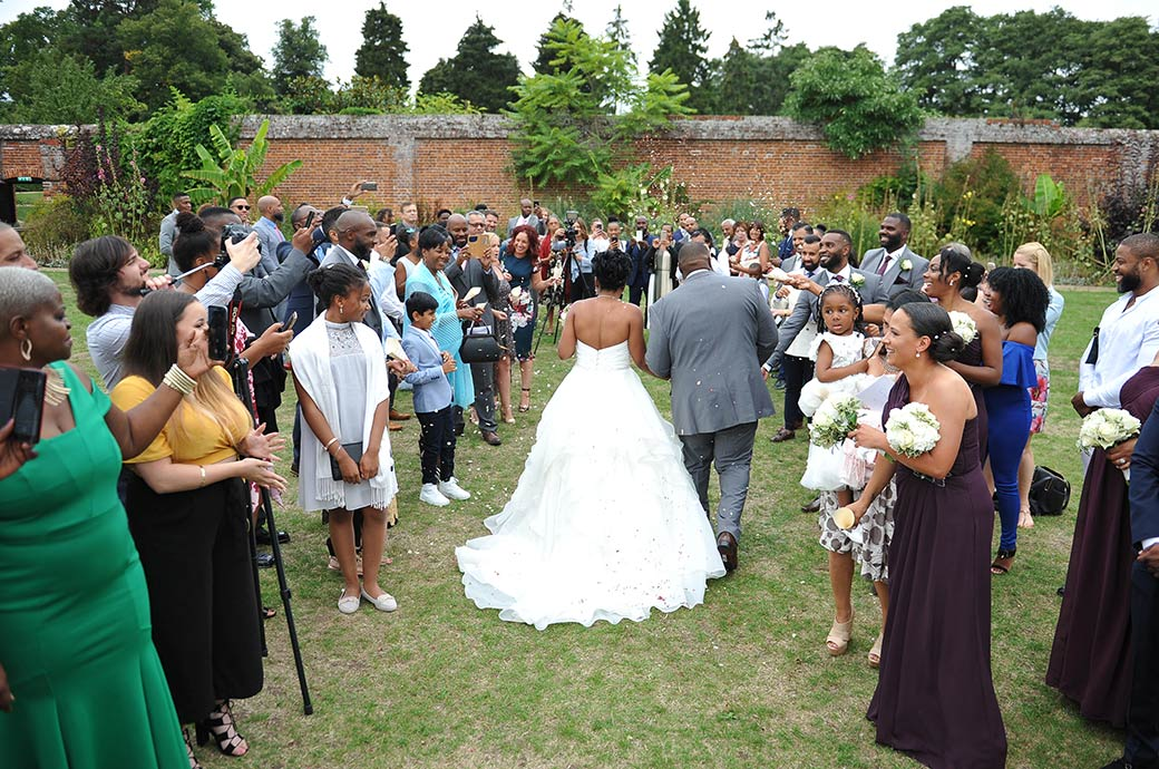 Fun for all the wedding guests outside The Conservatory in the Walled Garden as they throw confetti onto the newlyweds at Surrey venue Painshill Park