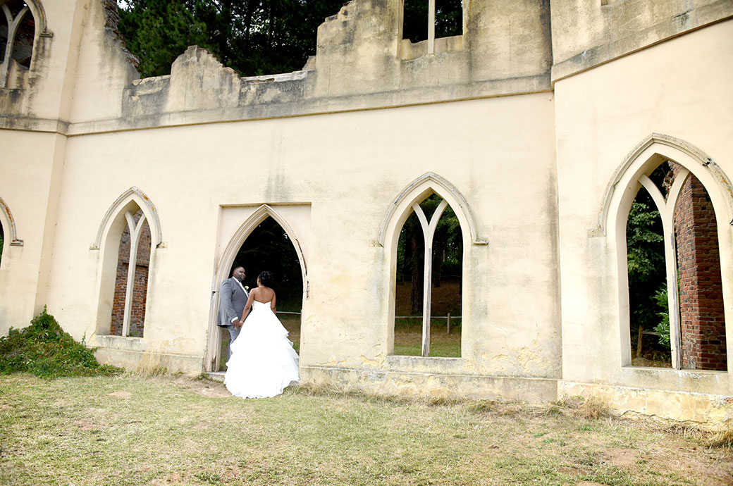 Bride and groom captured at the fascinating Surrey wedding venue Painshill Park as they stand in a doorway of the Ruined Abbey