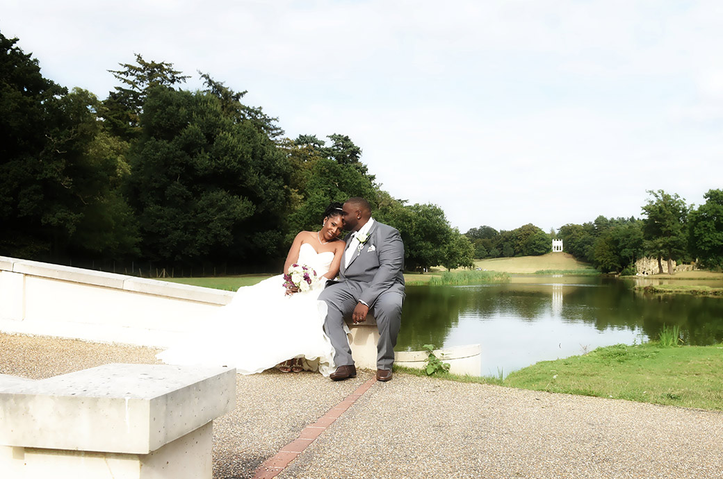 Romantic moment as Bride and groom sit on the Temple Five Arch Bridge at wonderful Surrey wedding venue Painshill Park with the Gothic Temple in the background