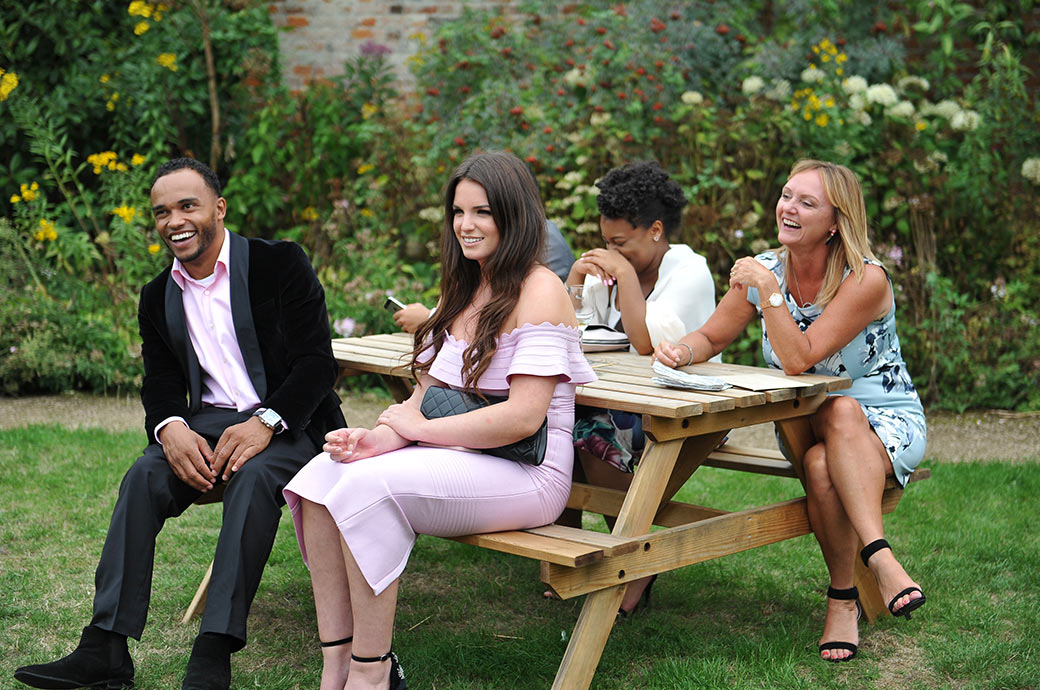 Wedding guests enjoying the banter at the informal Surrey venue Painshill Park as they relax during the drinks reception outside The Conservatory in the Walled Garden