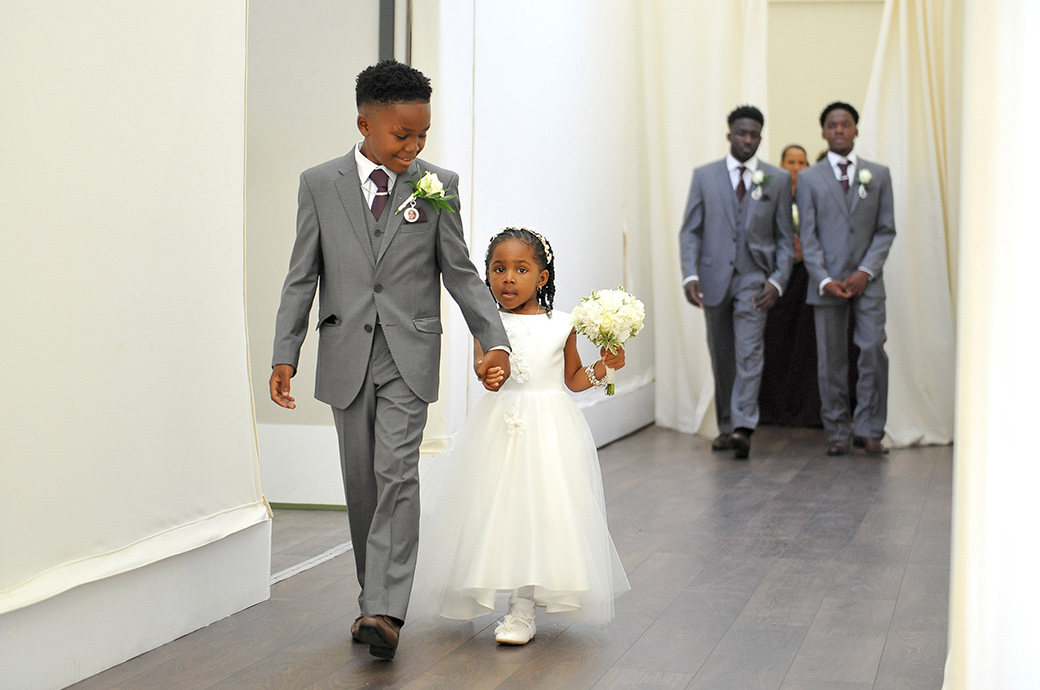 A cute little pageboy holding the hands of a sweet little bridesmaid pictured in Surrey wedding venue Painshill Park as they walk down the aisle of The Conservatory