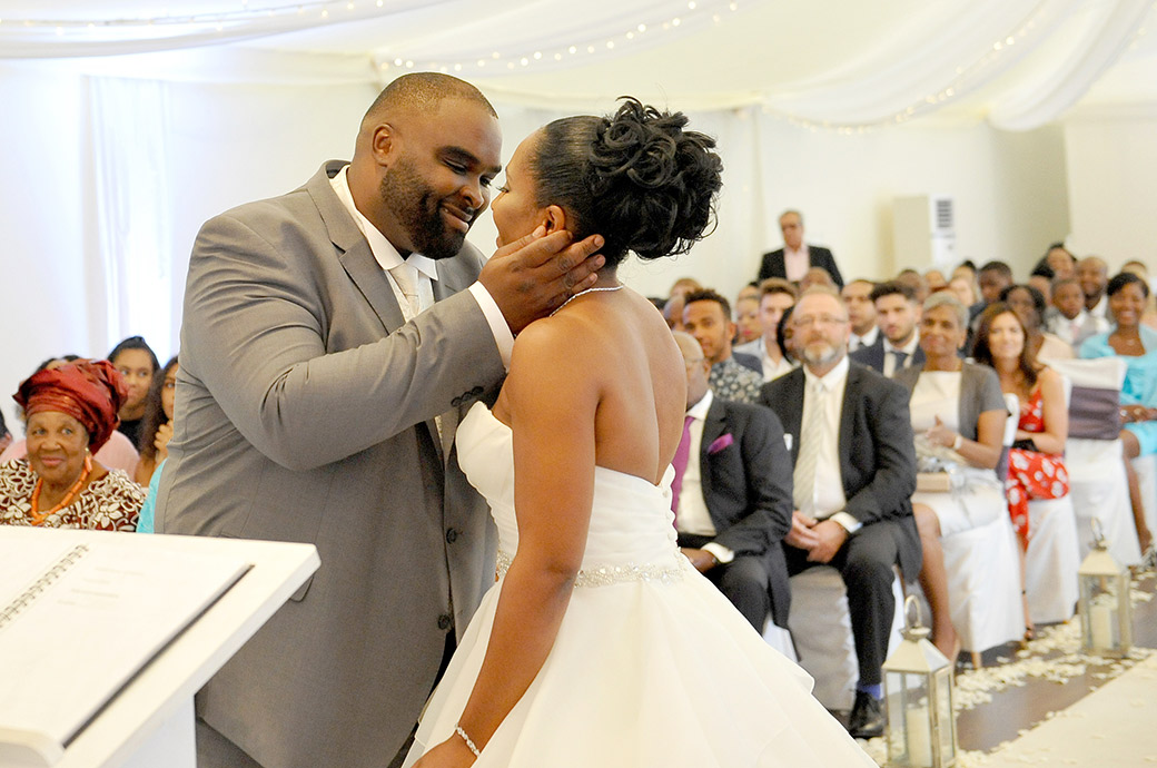 A loving Groom holds his Bride for a kiss as she meets him down the end of the aisle in The Conservatory at wedding venue Painshill Park Surrey