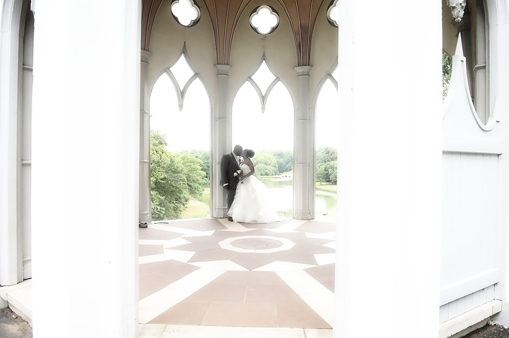 Newlyweds kissing in the romantic Gothic Temple with its wonderful views over the fascinating grounds of Surrey wedding venue Painshill Park