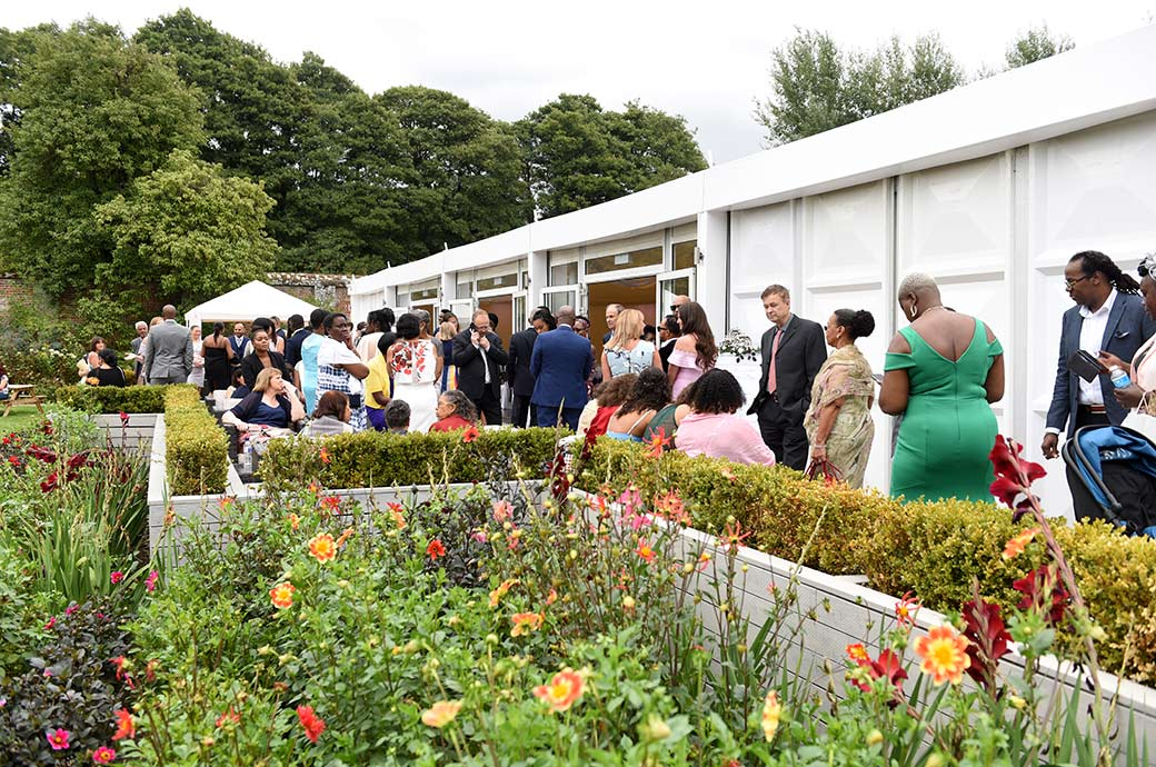 Pre marriage ceremony guests mingle outside The Conservatory in the Walled Garden at Surrey wedding venue Painshill Park