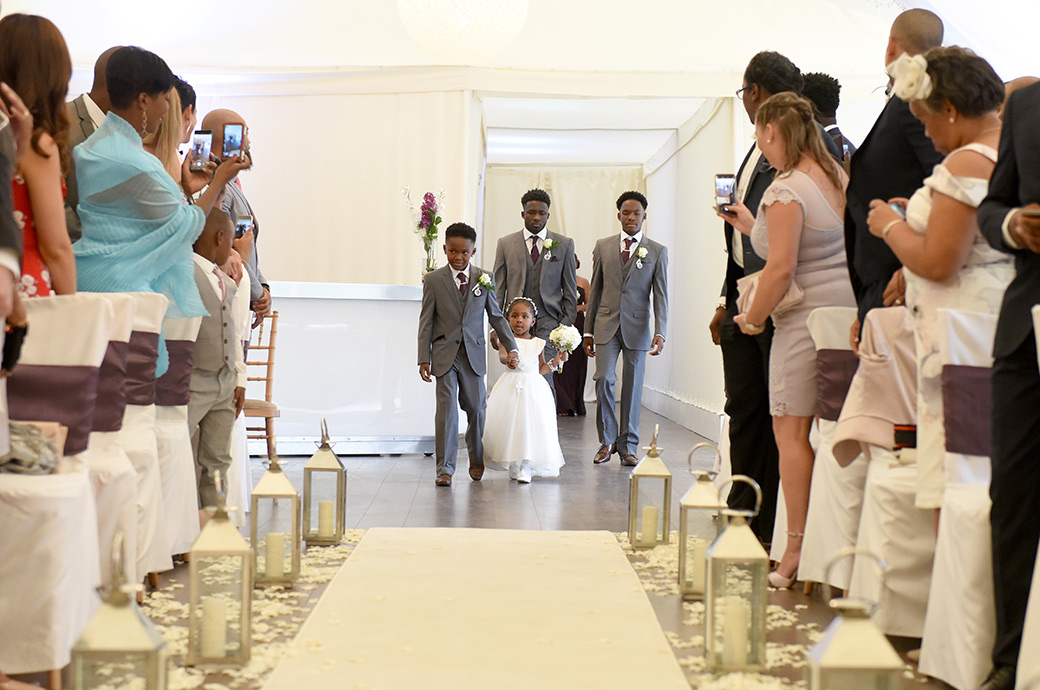 A view from down the aisle of The Conservatory Walled at Surrey wedding venue Painshill Park of a cute pageboy and bridesmaid leading the way for the young groomsmen