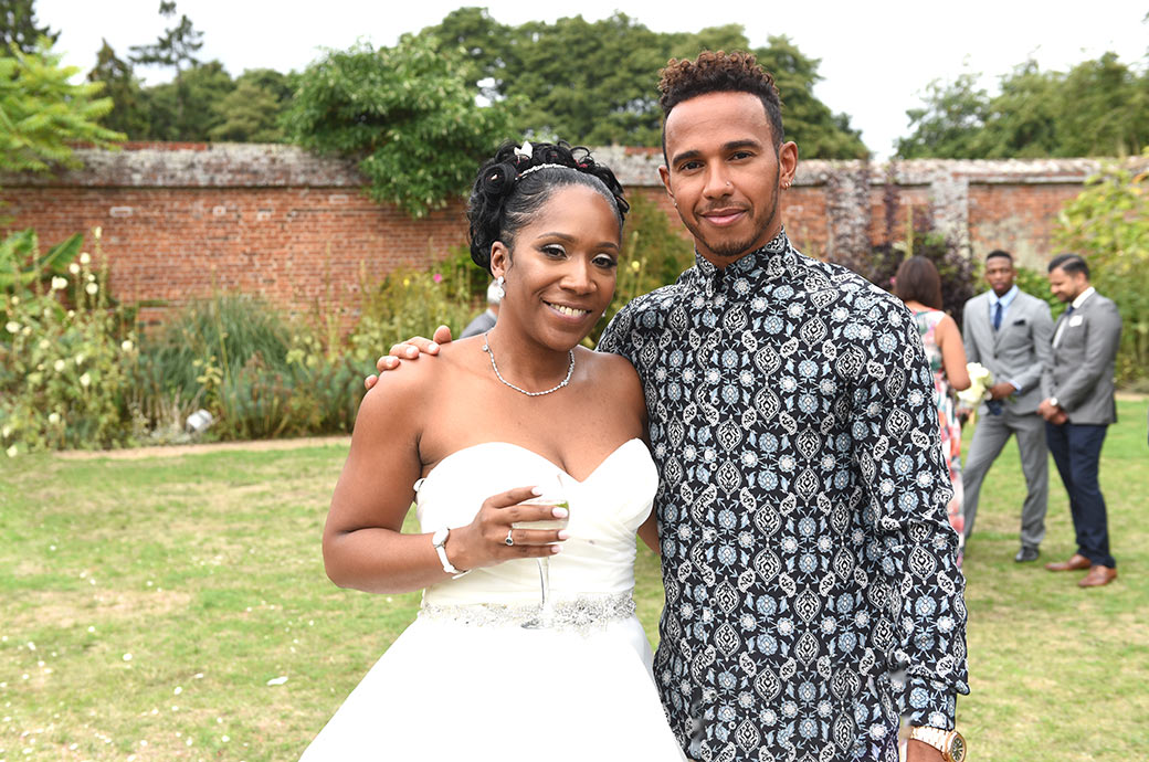 Bride in the Walled Garden at Painshill Park Surrey poses for a wedding photo with her famous cousin and four-time Formula One World Champion Lewis Hamilton