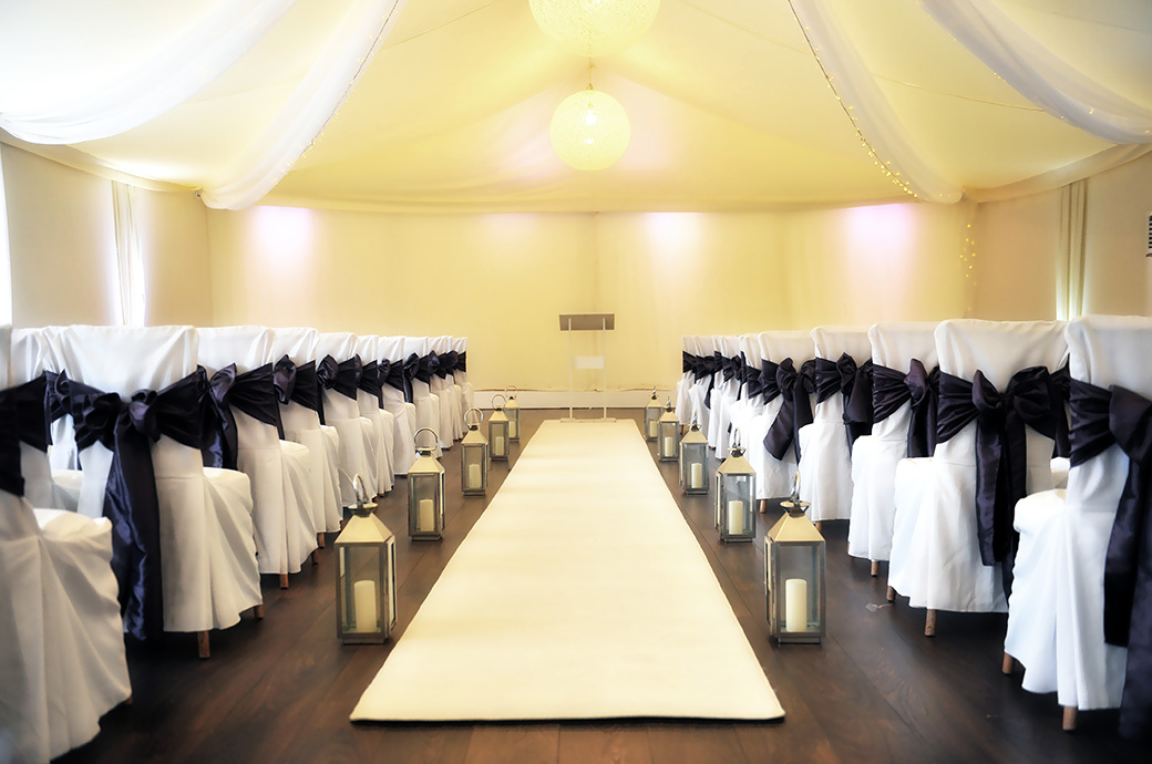 The aisle of the empty The Conservatory dressed with a white carpet and candle holders ready for the arrival of guests at the wonderful Surrey wedding venue Painshill Park in Cobham
