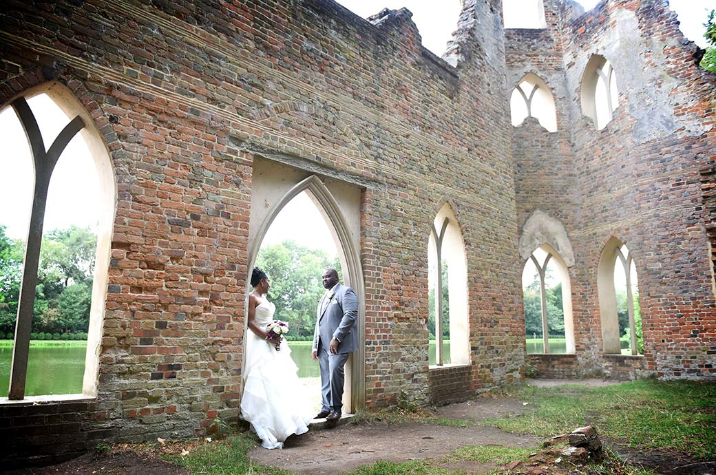 Newlywed couple stand on opposite sides of a doorway to the Ruined Abbey captured at the fascinating Painshill Park Surrey wedding venue