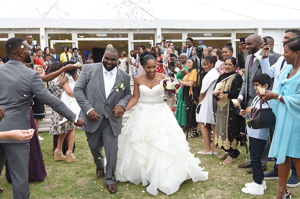 Smiling Bride and Groom have fun at Surrey venue Painshill Park as they walk across the lawn dodging the wedding confetti outside The Conservatory in the Walled Garden
