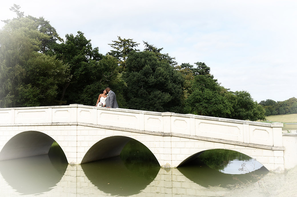 Bride and Groom kissing in this romantic picture taken in the grounds of Surrey wedding venue Painshill Park on the Five Arch Bridge