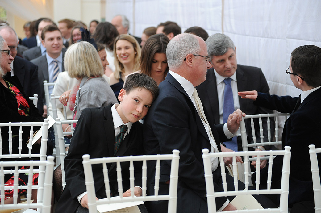 Funny picture of a little boy taken at Surrey wedding venue Pembroke Lodge resting his head on his dad as everyone awaits the arrival of the Bride