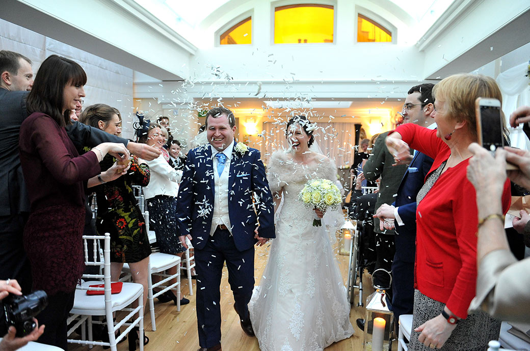 Newlyweds at Surrey wedding venue Pembroke Lodge have fun as they walk down the aisle of The Belvedere Suite into a shower of confetti