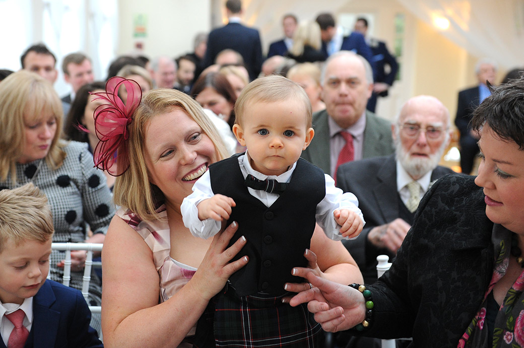 Cute little baby boy dressed smartly with Tartan held up for the photographer in The Belvedere Suite Surrey at the Pembroke Lodge wedding venue