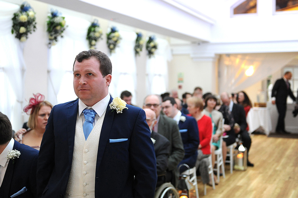 A nervous groom awaiting the arrival of the Bride in The Belvedere Suite at Surrey wedding venue Pembroke Lodge holding in his emotions as he stands in the aisle