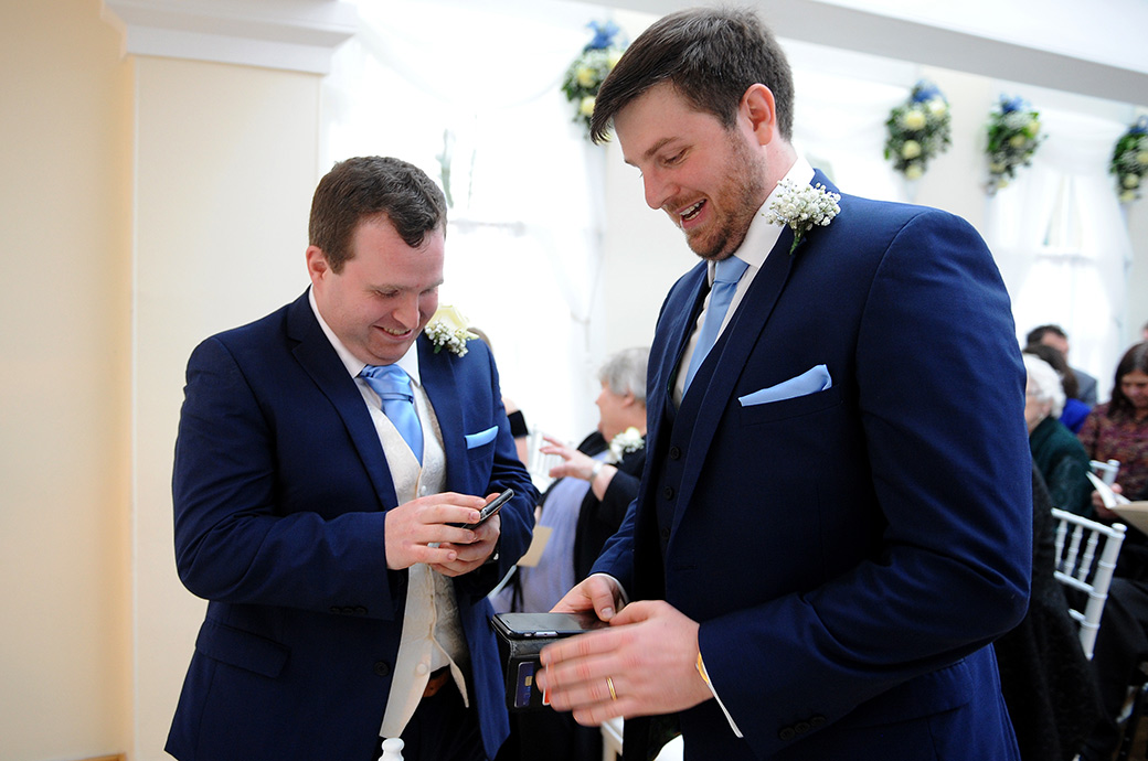 Groom and Best Man quickly turn off their mobile phones as they await the bride in The Belvedere Suite at Surrey wedding venue Pembroke Lodge in Richmond Park