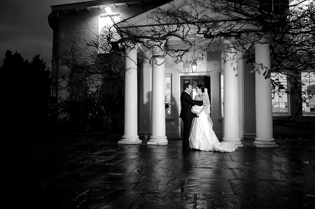 Nighttime embrace for a romantic couple as they stand by the pillars of the front entrance to Pembroke Lodge in Richmond Park Surrey