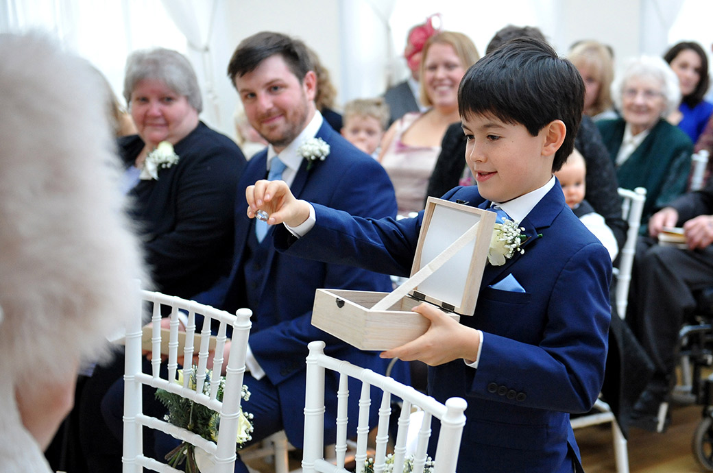Sweet and smart looking pageboy in The Belvedere Suite at Pembroke Lodge Richmond Park Surrey produces the wedding ring from a white wooden box
