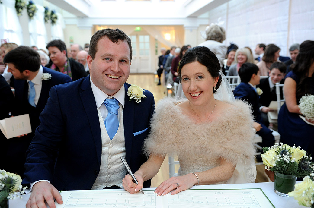 Smiling Bride and groom signing the marriage register in The Belvedere Suite at the Pembroke Lodge wedding venue in Richmond Park Surrey