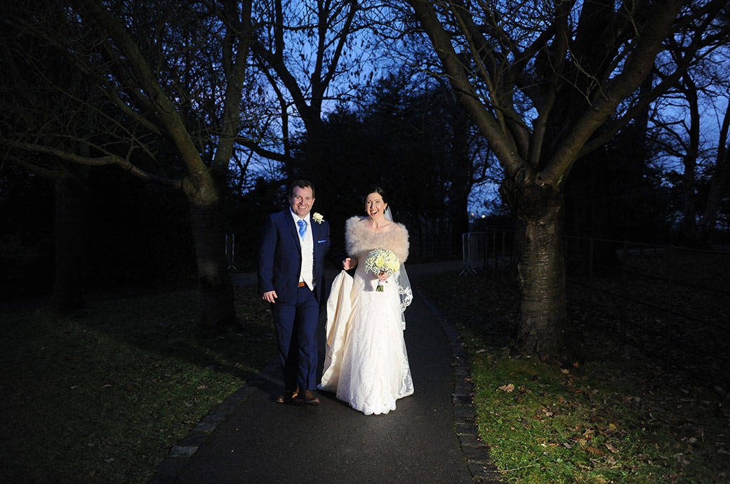 Happy newlyweds captured at Surrey wedding venue Pembroke Lodge as they walk along the path past The Belvedere Suite at night