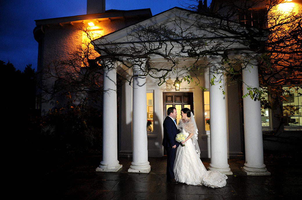 Bride and groom look into each others eyes by the pillared entrance to the atmospherically lit Pembroke Lodge wedding venue in Richmond Park Surrey