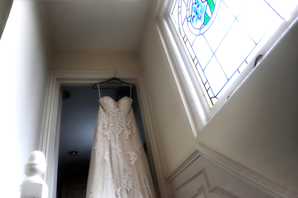 Bride's wedding dress hanging up by a stained glass window in her house before her marriage in The Belvedere Suite at Pembroke Lodge Surrey