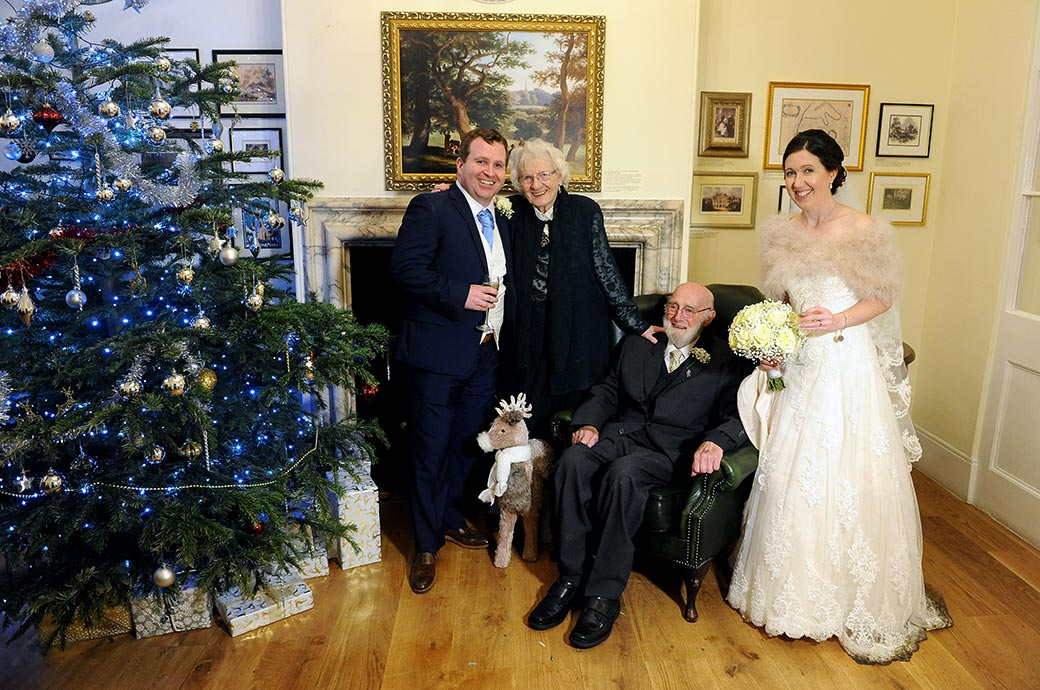 Bride and groom standing with grandparents around the lovely Christmas tree at the festive Pembroke Lodge wedding venue in Richmond Park Surrey