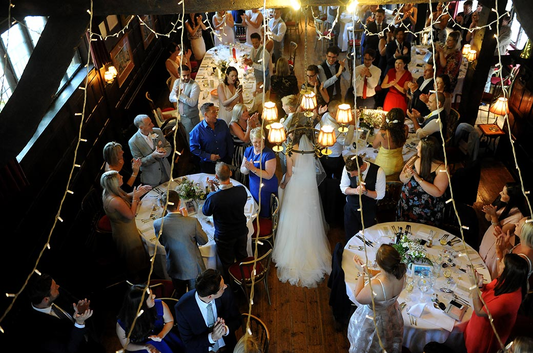 Bird's eye view of the guests applauding as the Bride and groom enter the Long Hall for their Ramster Hall wedding breakfast in the village of Chiddingfold Surrey