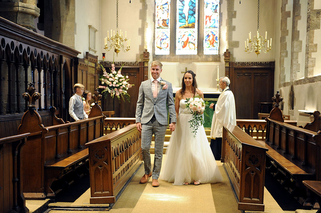 Happy newlyweds walk down the church aisle as husband and before leaving for their wedding reception at Ramster Hall Chiddingfold Surrey