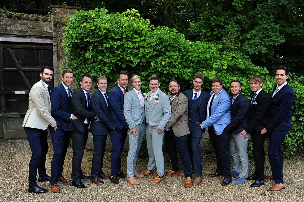 Laughing groom at Surrey venue Ramster Hall in Chiddingfold with gents having fun posing for a group wedding photo with their hands in each others pockets
