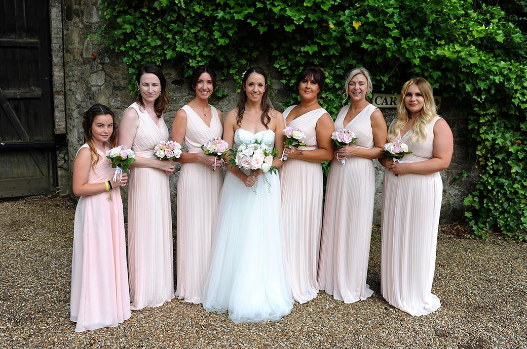 The lovely Bride out in the drive at Surrey wedding venue Ramster Hall with her six bridesmaids all in pink holding their mixed rose bouquets