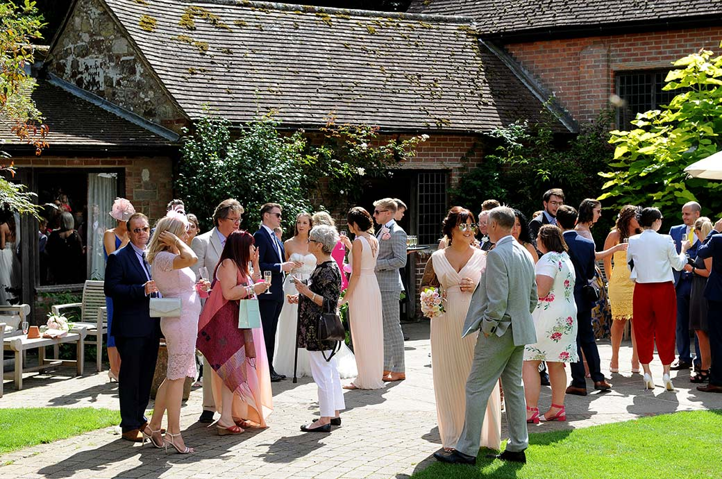 Wedding guests at the beautiful and rustic Surrey wedding venue Ramster Hall relax with drinks out in the lovely tranquil Courtyard Garden