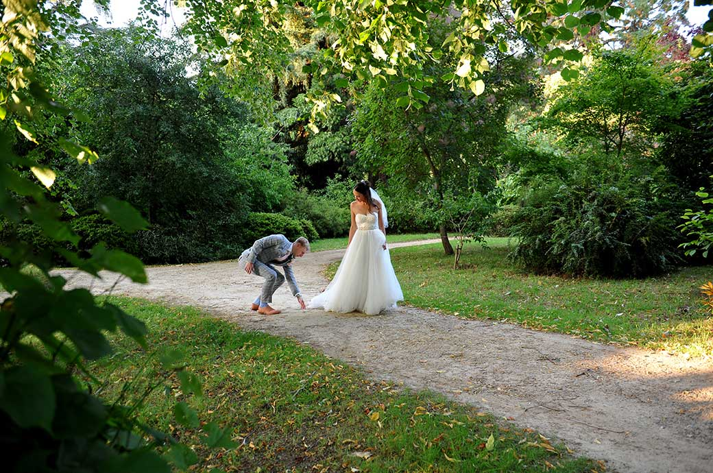 Touching and romantic wedding photograph of a groom helping his Bride with her dress as they walk across the grass in the Ramster Hall grounds Chiddingfold Surrey