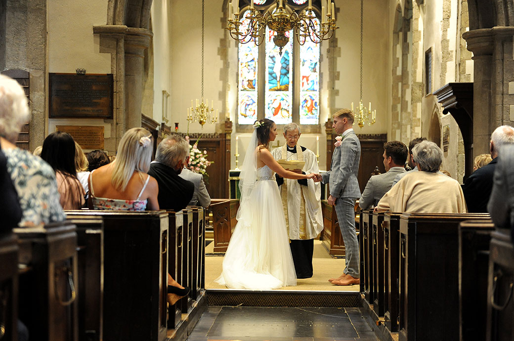Evocative wedding photograph of a bride saying her marriage vows in a Surrey church with the celebratory reception taking place later in Chiddingfold at Ramster Hall