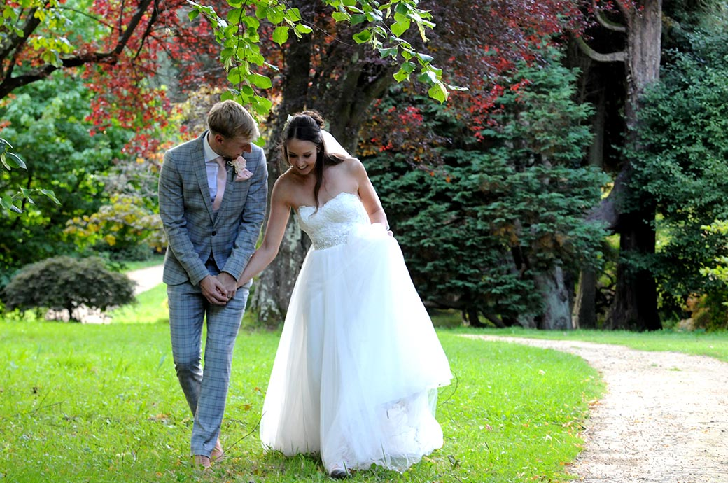 Groom holds onto his Bride's hand as they take a lovely relaxing romantic walk around the surrounding grounds of Surrey wedding venue Ramster Hall in Chiddingfold
