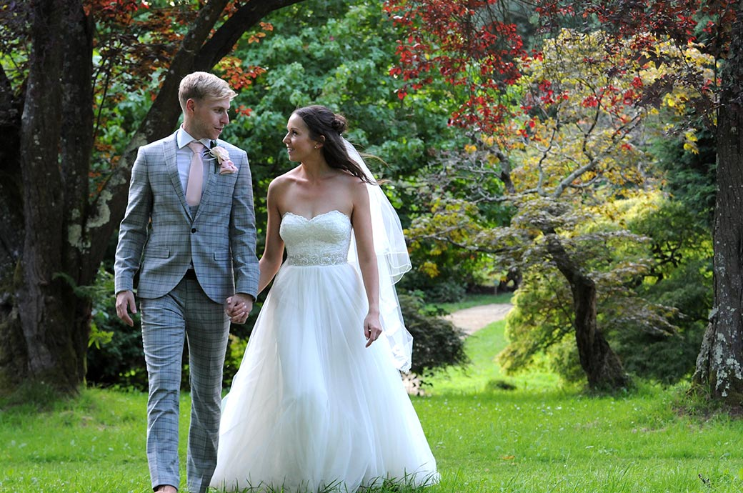 Loving looks exchanged as the excited Bride and groom at Surrey wedding venue Ramster Hall walk through the lovely green countryside hand in hand