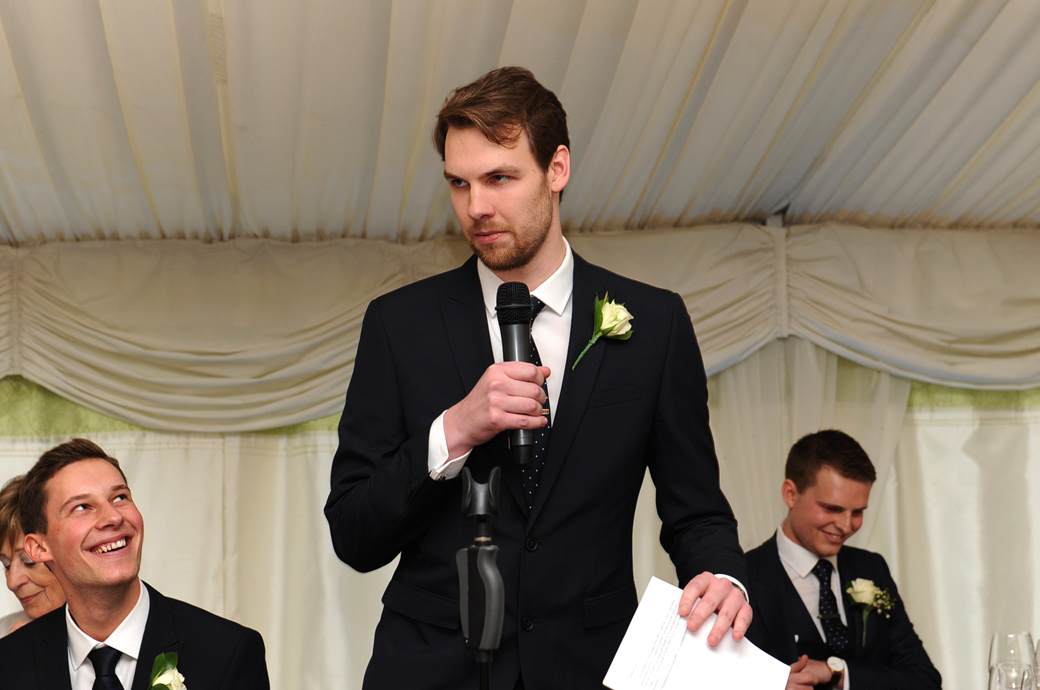 Best man gets into action as he delivers a very entertaining wedding speech taken at Surrey wedding venue Russets Country House in the charming village of Chiddingfold, Godalming
