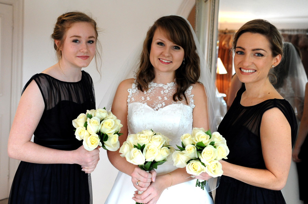 Smiling Bride and Bridesmaids with their bouquets captured in the bridal suite at Surrey wedding venue Russets Country House just before leaving  for the marriage ceremony