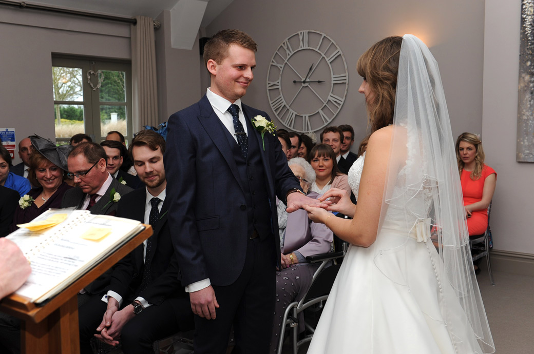 The Groom looks at his Bride as she holds the wedding ring on his finger and says her marriage vows in this Russets Country House wedding picture taken in the ceremony room