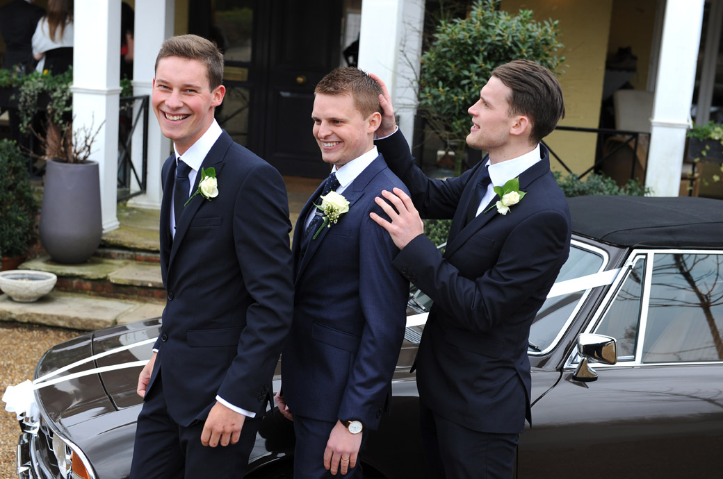 Fun time for the Groom and his brothers as they lark around in front of their dad's Triumph Stage car at the lovely Surrey wedding venue Russets Country House in Chiddingfold