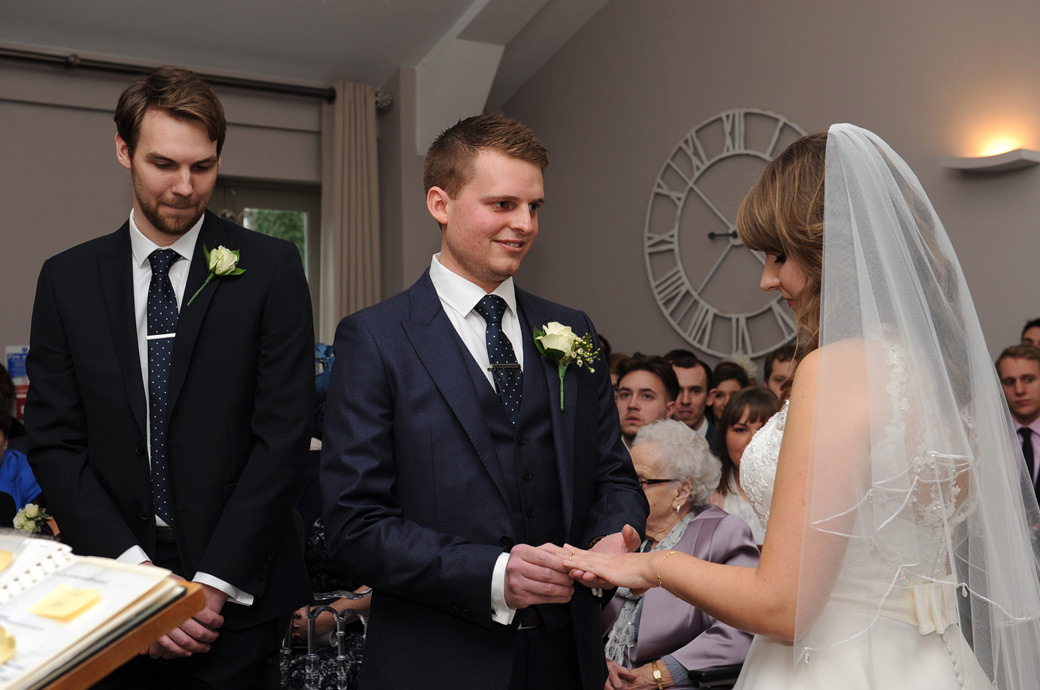 A loving look from the Groom as he holds his bride's finger captured in this wedding photograph taken at Surrey wedding venue Russets Country House in Chiddingfold, Godalming
