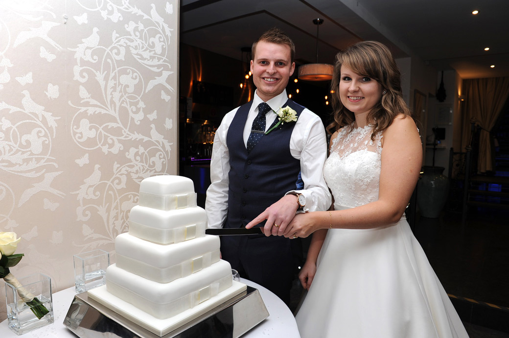 Happy newlywed couple at Surrey wedding venue Russets Country House pose for a classic cutting the cake wedding photo during the dinner celebrations