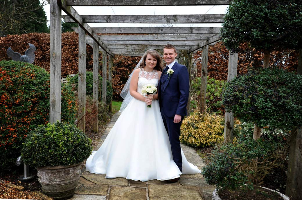Delighted newlywed couple stand together as husband and wife in the pretty arbour at the front entrance to Russets Country House a fine Surrey wedding venue in Chiddingfold village