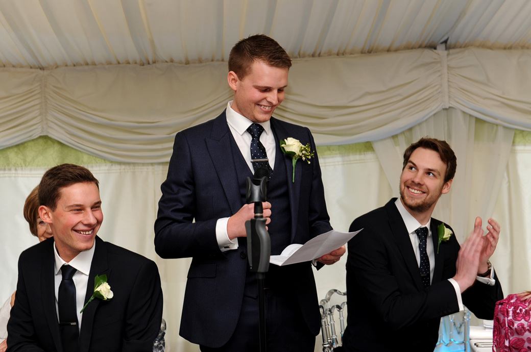 Smiles and applause from the Groomsmen as the groom begins his wedding speech during dinner in the fabulous Surrey wedding venue Russets Country House